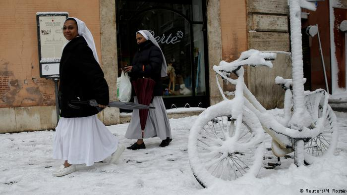 Nuns walk by snow covered bikes.