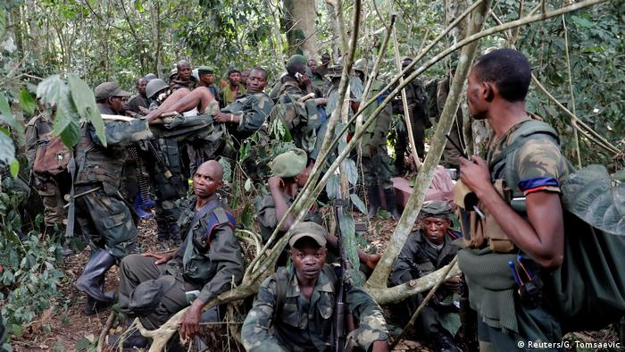 A group of Congolese soldiers, one wounded on a stretcher, take a rest in the jungle