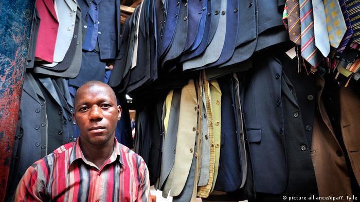 ein Altkleider-Händler auf dem Owino Markt in Uganda vor seinem Kleiderstan