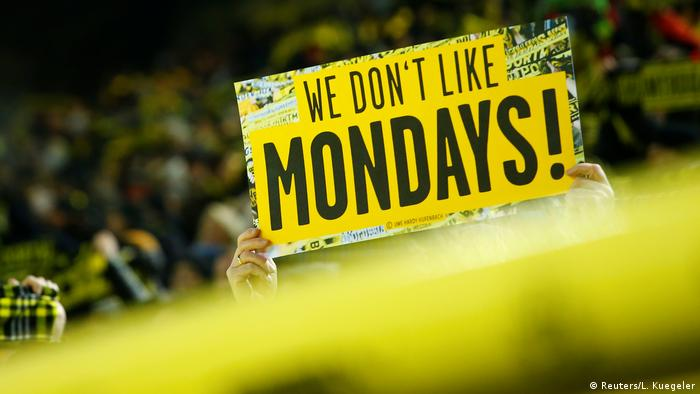 Borussia Dortmund fans hold up a banner before the match reading We don't like Mondays!