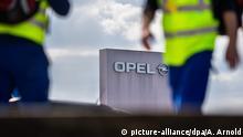 ARCHIV - 06.04.2017, Hessen, Rüsselsheim: Zwei Männer in gelben Sicherheitswesten gehen am Stammwerk von Opel vorbei. (zu dpa: Opel-Sanierung kommt an deutschen Standorten kaum voran vom 26.02.2018) Foto: Andreas Arnold/dpa +++(c) dpa - Bildfunk+++ | Verwendung weltweit