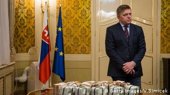 Robert Fico behind a table full of money