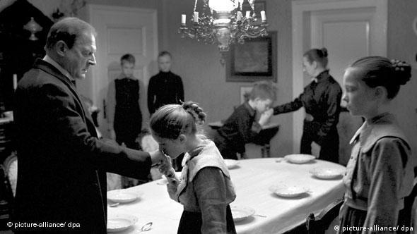 Der Pfarrer läßt sich von einem Kind die hand küssen, im Hintergrund Familie (Les Film du Losange/dpa)