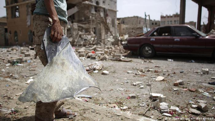 Ein schiitischer Rebell, bekannt als Houthi, hält ein Metallfragment neben den Trümmern von Häusern, die von einem saudisch geführten Luftangriff in Sanaa im Jemen zerstört wurden
