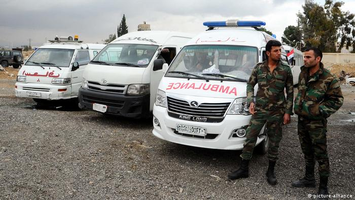 Syrian Red Crescent ambulances wait at a designated point to evacuate ill civilians from Eastern Ghouta