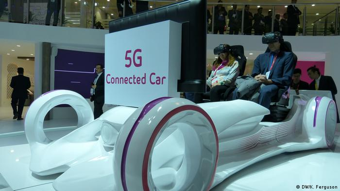Two people sit in a model of a 5G connected car of the future at the Barcelona Mobile World Congress in 2018 (DW/K. Ferguson)