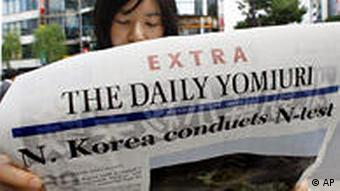 A pedestrian reads an extra edition of a Japanese newspaper reporting North Korea's nuclear test in Tokyo, Japan, Monday, May 25, 2009.