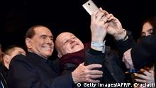 25.02.2018 +++ Leader of Italian right-wing party Forza Italia (Go Italy) Silvio Berlusconi (L) poses with a supporter for a selfie picture at the end of a campaign rally in Milan on February 25, 2018, ahead of the Italian general elections of next week. Silvio Berlusconi, the billionaire media mogul who dominated Italian politics for nearly two decades, has stepped back into the ring at the age of 81, defying those who dared to believe he had thrown in the towel. Despite sex scandals, serial gaffes and legal woes, the flamboyant tycoon has made an astonishing return from political oblivion to head his centre-right Forza Italia (Go Italy) party, which as part of a rightwing coalition is leading the race for the March 4, 2018 vote. / AFP PHOTO / Piero CRUCIATTI (Photo credit should read PIERO CRUCIATTI/AFP/Getty Images)