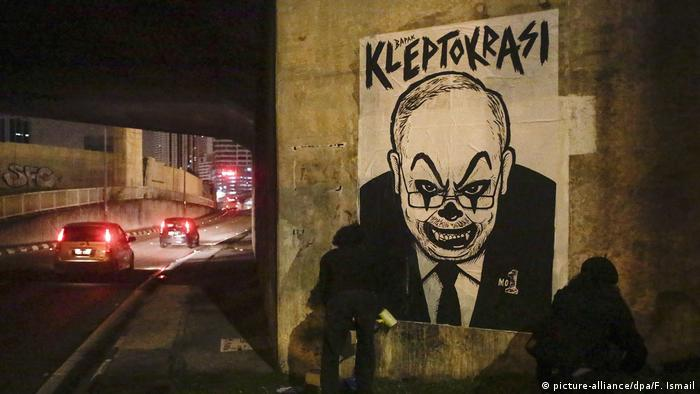 Activist and artist Fahmi Reza (R) and his friend mount a caricature poster depicting Najib with a clown face ahead of a rally in Kuala Lumpur, Malaysia.