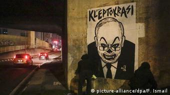 Poster depicting Najib Razak in clown makeup with the world kleptocracy above it