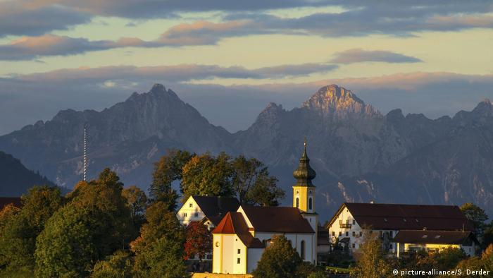 The Alps loom in the distance, in the foreground a small Bavarian chapel