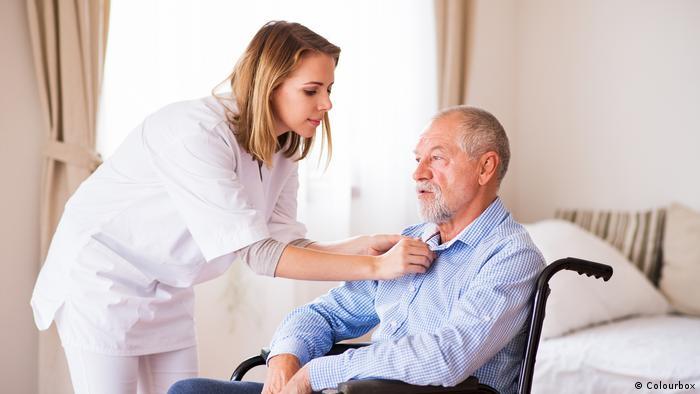 Symboldbild Krankenschwetser untersucht Mann in Rollstuhl