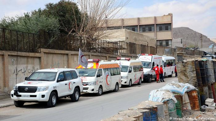 Syrian Red Crescent ambulances wait at a designated point to evacuate the ill civilians from the fighting Eastern Ghouta countryside.
