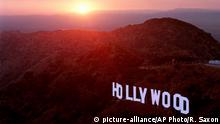 FILE- This June 30, 1999 file photo shows the sun setting behind mountains as the Hollywood sign overlooks Los Angeles. For a century and a half California has been a destination for every conceivable sort of adventurer. (AP Photo/Reed Saxon, File) |