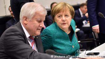 Seehofer and Merkel sit at a table next to one another