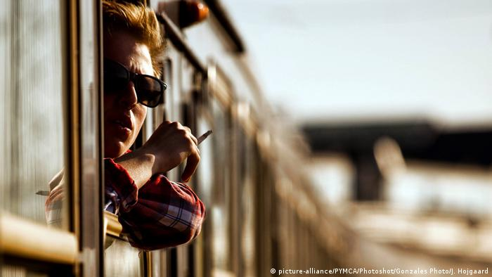 A man leans out the train window and smokes a cigarette