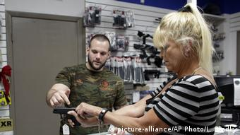 A man helps a woman try out a handgun in a store