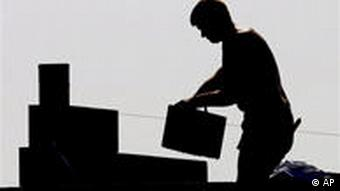 A silhouette of a worker stacking boxes