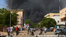 02.03.2018 +++ TOPSHOT - People watch as black smoke rises as the capital of Burkina Faso came under multiple attacks on March 2, 2018, targeting the French embassy, the French cultural centre and the country's military headquarters. Witnesses said five armed men got out of a car and opened fire on passersby before heading towards the embassy, in the centre of the city. Other witnesses said there was an explosion near the headquarters of the Burkinabe armed forces and the French cultural centre, which are located about a kilometre (half a mile) from the site of the first attack. / AFP PHOTO / Ahmed OUOBA (Photo credit should read AHMED OUOBA/AFP/Getty Images)