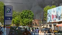 02.03.2018 +++ People watch as black smoke rises as the capital of Burkina Faso came under multiple attacks on March 2, 2018, targeting the French embassy, the French cultural centre and the country's military headquarters. Witnesses said five armed men got out of a car and opened fire on passersby before heading towards the embassy, in the centre of the city. Other witnesses said there was an explosion near the headquarters of the Burkinabe armed forces and the French cultural centre, which are located about a kilometre (half a mile) from the site of the first attack. / AFP PHOTO / Ahmed OUOBA (Photo credit should read AHMED OUOBA/AFP/Getty Images)