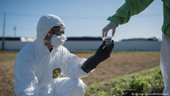 Pessoa com roupas de proteção coleta amostra de terra