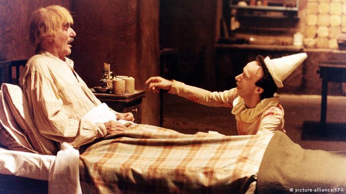 Roberto Benigni als Pinocchio knieend am Bett eines Mannes (picture-alliance/KPA)