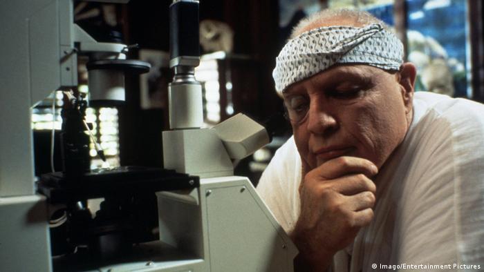 Marlon Brando als Dr. Moreau an einem Mikroskop im Film DNA - Die Insel des Dr. Moreau. (Imago/Entertainment Pictures)