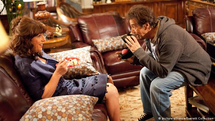 Adam Sandler als Frau verkleidet und Al Pacino sitzen sich in Jack and Jill in einem Wohnzimmer gegenüber. (picture-alliance/Everett Collection)