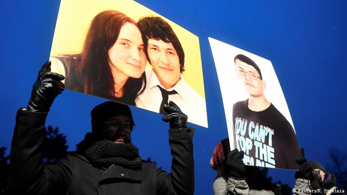 Protesters hold up pictures of Kuciak and his fiancée