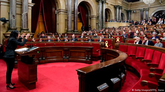 Politicians sit and listen to a speaker in the Catalan parliament