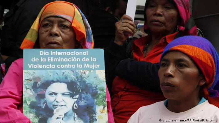 Protesters hold placards demanding an end to violence against women with an image of Berta Caceres
