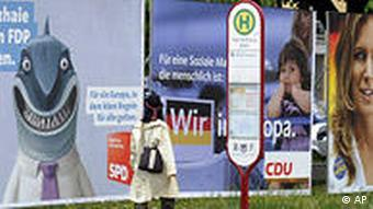 A woman walks along a line of election posters for the upcoming European elections, in Freiburg, southern Germany