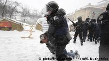 Riot police detain a protester as they assault a tent camp installed by activists of the Movement of New Forces, the political party led by Mikheil Saakashvili, as protesters fire tires in Kiev, Ukraine early Saturday, March 3, 2018. Protesters demand President Petro Poroshenko's impeachment. (AP Photo/Serhii Nuzhnenko)  