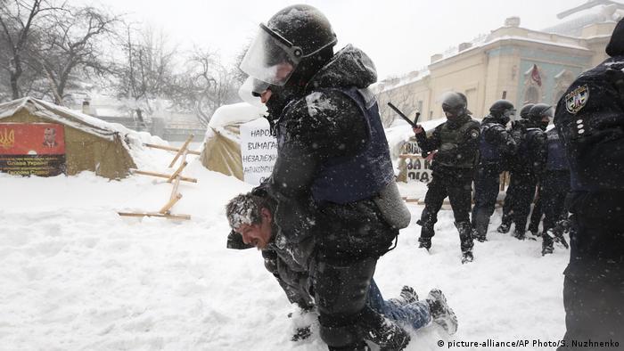 Полицейские тащат протестующего