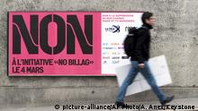 FILE - In this Feb. 9, 2018 photo a man passes by a sign asking to vote in the No Billag initiative in Fribourg, Switzerland. Swiss voters can decide in a referendum on March 4, 2018 on a proposal to stop the mandatory licence fee for services of the Swiss Broadcasting Corporation. (Anthony Anex/Keystone via AP)  