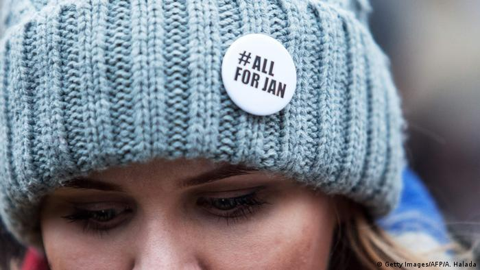 A woman has a pin's on her woolly hat during a silent protest march to pay tribute to murdered Slovak journalist Jan Kuciak