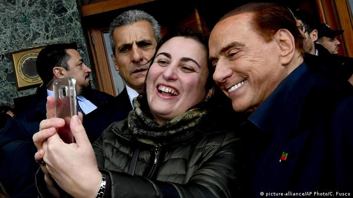 Former Prime Minister Silvio Berlusconi takes a picture with a fan in Naples