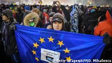 A man holds an EU flag during a protest against the Justice minister and the corruption in the front of the Romanian Government in Bucharest on February 25, 2018. Romania's justice minister Tudorel Toader launched on Thursday a procedure to sack the popular and internationally respected head of the anti-corruption investigation body. Toader, from the left-wing Social Democratic Party (PSD) said that the head prosecutor of DNA (National Anticorruption Department), Laura Codruta Kovesi had damaged the image of Romania abroad and accused her of being authoritarian. Kovesi has helped bring a raft of corrupt officials to justice in recent years in one of the EU's most graft-ridden countries. / AFP PHOTO / Daniel MIHAILESCU (Photo credit should read DANIEL MIHAILESCU/AFP/Getty Images)