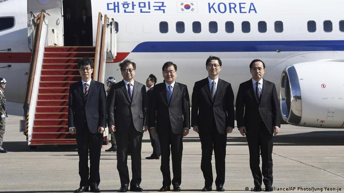 South Korean officials stand in front of a plane before flying to North Korea