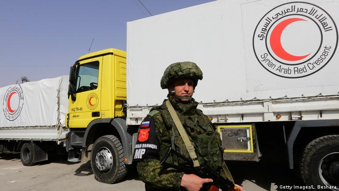 A Russian solider stands guards as Syrian Arab Red Crescent vehicles carrying aid wait at the al-Wafideen checkpoint on the outskirts of Damascus neighbouring the rebel-held Eastern Ghouta region before delivering aid to the rebel-held enclave