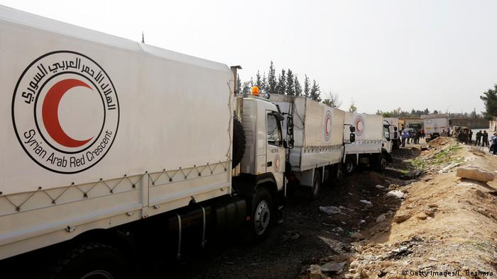 Syrian Arab Red Crescent vehicles carrying aid wait at the al-Wafideen checkpoint on the outskirts of Damascus neighboring the rebel-held eastern Ghouta region before delivering aid to the rebel-held enclave