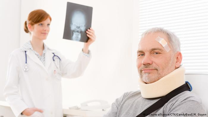 Female doctor holding up X-ray while male patient sits with a brace around his neck and a bandaid on his forehead (Copyright: picture-alliance/CTK/CandyBox/M. Guyon)