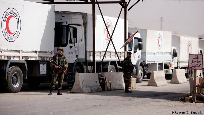 Soldados junto a caminhões do Crescente Vermelho