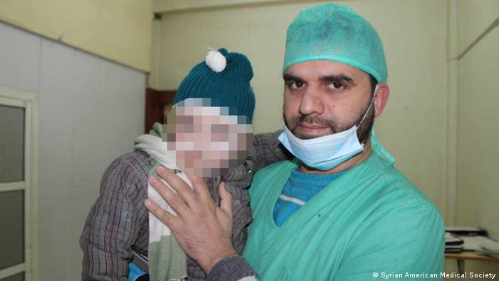 A doctor in Eastern Ghouta holding an injured child (Syrian American Medical Society)