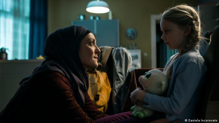 Film still, a woman kneels in front of a young girl with a stuffed animal (Daniela Incoronato)