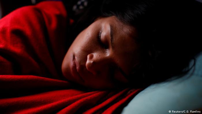 Alejandra Rodríguez duerme mientras viaja en el autobús rumbo a Chile, el 14 de noviembre de 2017. Finalmente, después de siete días de viaje atravesando cinco países, ha encontrado una posición cómoda para dormir en su asiento. O quizás estaba tan cansada que ya no le importaba cómo dormía.