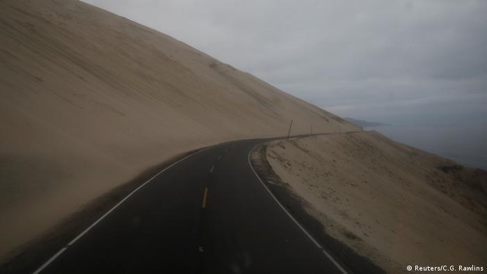 La carretera serpentea junto al mar en Atico, Perú, el 13 de noviembre de 2017, mientras Carlos García Rawlins disfruta de la vista desde la primera fila en el piso superior del autobús. Dijo sentir a veces un sentimiento de vacío mientras el camino desaparecía detrás de una curva y la niebla descendía, cubriendo el horizonte.