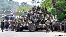 Sri Lanka's army soldiers stand guard a road after a clash between two communities in Digana, central district of Kandy