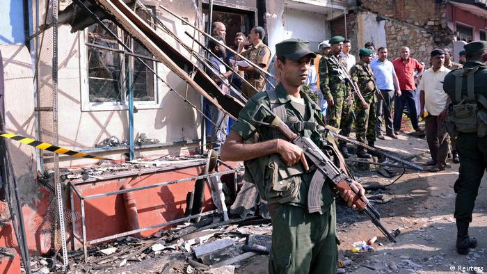 Sri Lanka's army soldiers stand guard near a burnt house