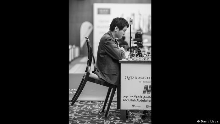 Wesley So seated at the chess board with his chair leaned forward (Photo: David Llada)